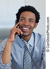 Attractive smiling Afro-American businessman on phone in office