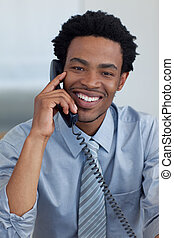Portrait of smiling Afro-American young businessman on phone in office