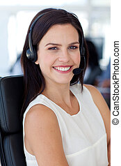 Businesswoman with a headset smiling to the camera