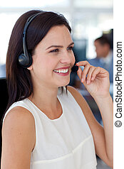 Businesswoman talking on a headset in a call centre -...