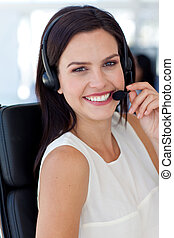 Smiling businesswoman talking on a headset in a call centre