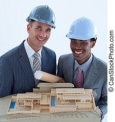 Smiling engineers with hard hats holding a model house -...