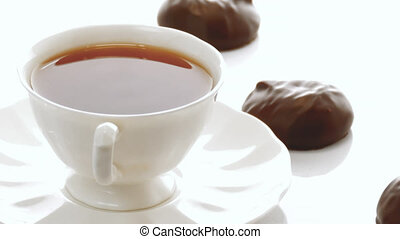 chocolate covered marshmallows on white background and a cup...