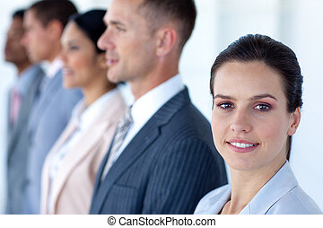 Confident businesswoman with her team in a line looking at...