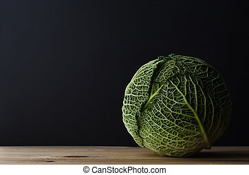 Whole Cabbage on Wooden Table - A whole head of leafy green...
