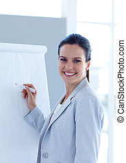 Smiling businesswoman writing in a whiteboard