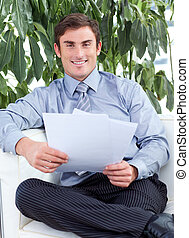 Businessman reading papers and smiling at the camera -...