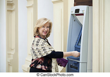 Mature blonde woman with credit card in hand near ATM -...