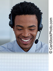 Smiling Afro-American businessman talking in a call center -...