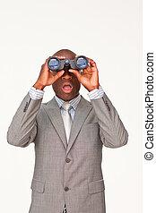 Surprised Afro-American businessman looking through binoculars