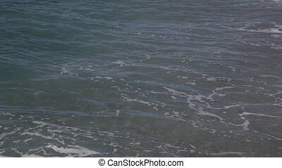 Sea waves with white foam break about the coast during a...