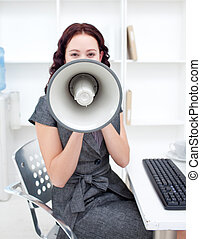Attractive businesswoman yelling through a megaphone in...