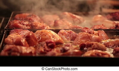 Appetizing slices of meat are fried on a big baking sheet,...