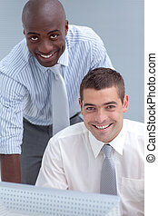 Two businessmen using a computer in office - Caucasian and...