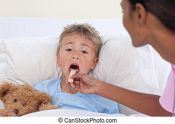 Nurse checking little boy throat in hospital - Ethnic nurse...