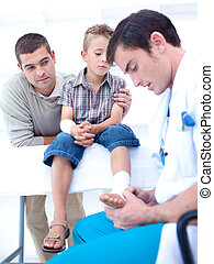 Doctor bandaging a patient\'s foot in hospital