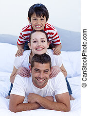 Happy parents and son playing in bed together