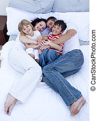High view of parents and children relaxing in bed together