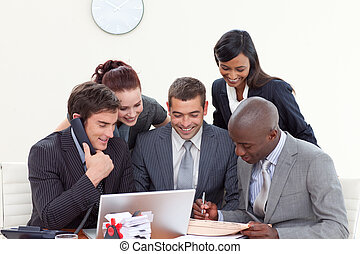 Business people in a meeting using a telephone and a laptop...