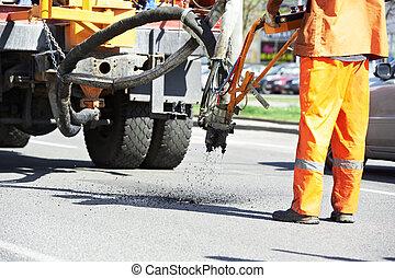 Asphalt patching roadworks - Road worker at asphalt roadway...