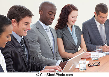 Business people in a meeting taking notes and using a laptop