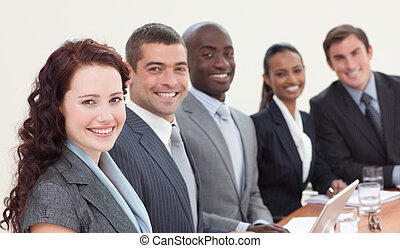 Business people sitting in a meeting and smiling at the...