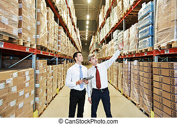 warehouse crew at work - two managers workers in warehouse...