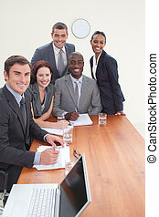 Five business people in a meeting smiling at the camera all...