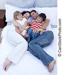 High view of family relaxing in bed together