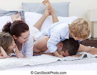 Happy young family playing in bed