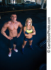 Group of a man and woman in crossfit gym - Full length...