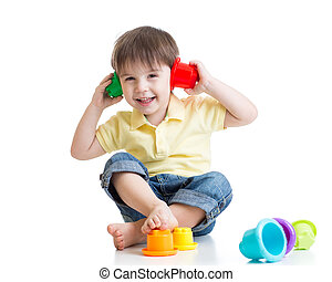 little kid is playing with toys while sitting on floor, isolated over white