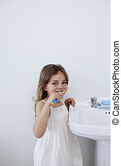 Little girl cleaning her teeth in bathroom with copy-space -...