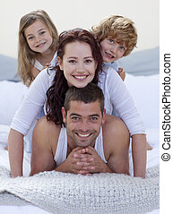 Portrait of happy family having fun in bed together
