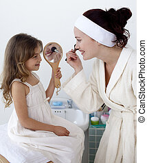 Daughter helping her mother in makeup