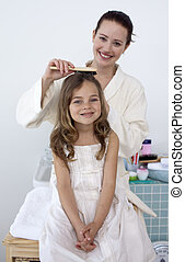 Mother doing her daughter\'s hair