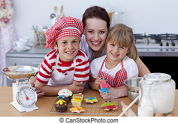 Smiling mother and children baking in the kitchen - Smiling...