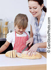 Mother and daughter cutting bread in kitchen