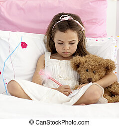 Little girl writing in bed