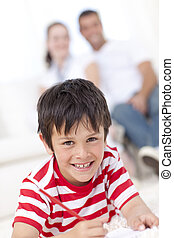 Smiling kid painting on floor in living-room