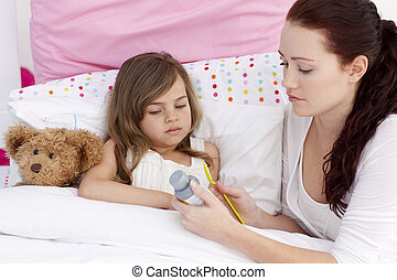 Little girl in bed taking cough sirup with her mother -...