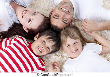 Family on floor with heads together - Family lying on floor...