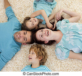 Smiling family on floor with heads together