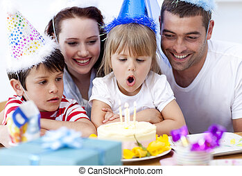 Little girl blowing out candles in her birthday with her...