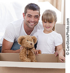 Father and daughter with a teddy bear moving home