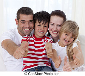 Portrait of smiling family sitting on sofa together with...