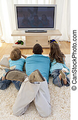 Father and children watching television in living-room