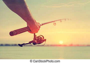 Fishing - Hand with a fishing tackle against the beautiful...