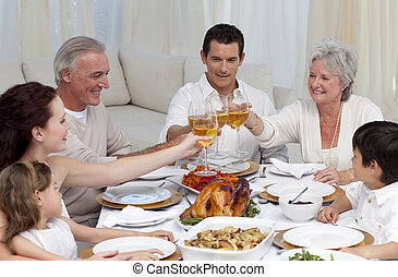 Family tusting with wine in a dinner