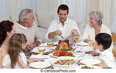 Father serving turkey to his family in a dinner